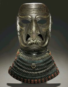 Karasu TenguSomen(Full Face Mask). Meiji period (19th century), JapanRusset-iron mask constructed from four sections hammered with prominent wrinkles, eyebrows and cheekbones, decorated on the surface with gold lacquer inmokumeand with highlights around the wrinkles and brow, the long beak decorated with the Sanskrit character representing Fudo Myo-o and stylized flames, cheeks with applied cord rings, interior lacquered black; fitted with a four-lame throat guard laced in blue and…