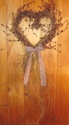 """This primitive, country grapevine twig heart with trailing vine and burgundy berries all around the heart is tied with a burgundy homespun bow would make a great addition to your Valentine's Decor. Heart measures approx. 34"""" long from top to bottom."""