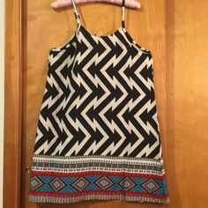 NWOT geometric print dress/tunic size L Black and white geometric print and tribal print border dress is made from 100% polyester, but looks and feels like silk. Wear as a dress or tunic. Underarm to underarm 18 3/4 inches. Shoulder to bottom of dress 27 3/4 inches Dresses