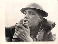 1940- Soldier of the British Grenadier Guards in France using his teeth to pull the pin of a hand grenade.