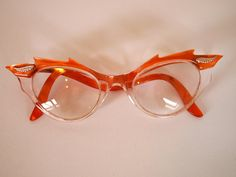 Vintage 1950s decorative flame style detail pearlescent orange and clear cat eye glasses with pink metallic detail. £50.00, via Etsy.