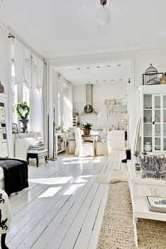 Love, love, love this white painted wood floor, white decor, sisal type rug and old dresser/unit.