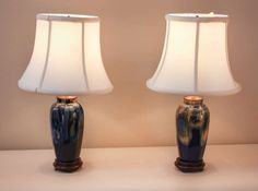 Pair of 1930s Pottery lamps featuring a blue glaze with yellow and green highlights. Each lamp sits on a beautiful wooden base and has a new, pure silk lampshade