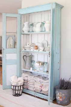A rustic armoire is given a fresh coat of pale turquoise paint and becomes a handsome showcase for vintage pitcher and linen collections.