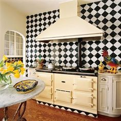 Modest Kitchen with Aga Stove  A traditional English-made Aga stove replaced the previous cooktop. The wall behind is set with a bold pattern of white and green tiles with chamfered edges for texture and color.