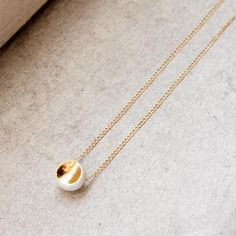 Solar Necklace (2 styles)  Solar Necklace  A spherical-shaped, concave drop with a mirror like appearance strung through a delicate 14k yellow or rose gold chain. A perfect piece for both layering and wearing on its own.