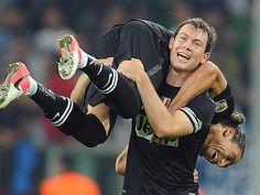 Juves Stephan Lichtsteiner trägt seinen Turiner Kollegen Martin Caceres nach dessen Führungstor im Spitzenspiel gegen Neapel über den Platz. Juve führt nach dem 2:0-Sieg nun die italienische Serie A an. (Foto: Di Marco/dpa)