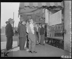 """Reading bulletins in Japanese language in """"Little Tokyo"""" when residents of Japanese ancestry were instructed to evacuate. They will be assigned to War Relocation Authority centers for the duration. 11 April 1942, Clem Albers, public domain via Wikimedia Commons."""