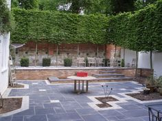 Stylish courtyard, mixed pavers for definitions, multi-funtional, water wall behind table, I hope