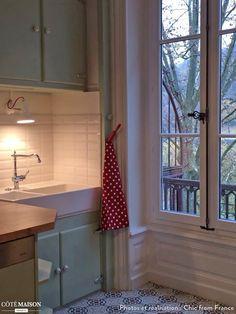 Une cuisine retro aux couleurs pastels et des carreaux de ciments qui recouvrent le sol.
