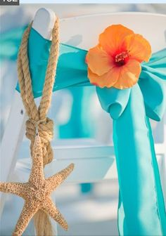 Like the addition of the fresh flower to the chair bow. Nice pop of color... and the starfish makes it very beachy!