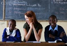 Two students sitting with the teacher in classroom, Kenya