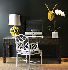 Chic office space with bold black walls paint color, white faux bamboo chair, Kenneth Wingard Yellow Truffault Lamp, ornate desk and orchid.