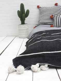 Tassel Stripe Pom Pom Blanket by Bohemia Design. A handwoven Moroccan cotton throw in black with white stripes, decorated with chunky cotton pom poms and tassel detail. Working in ethical partnership with traditional Moroccan weavers, Bohemia Design has created a colorful collection of Berber Pom Pom blankets in 100% natural wool and cotton. The blankets are woven entirely by hand on wooden looms and decorated with giant poms poms in classic Berber style.