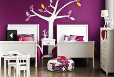 This modern room with a dark purple wall is brightened up with the use of white everywhere else.