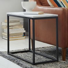 The slim profile of the Box Frame Side Table lets you save precious space in smaller living rooms and bedrooms. Its steel base and solid marble top add some polish to your space.