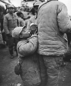 A kid nationalist soldier drinking from the kettle.  1948年11月, 上海,从北方前线撤下的一童军喝着同伴水壶里的水。