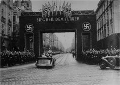"Adolf Hitler acknowledges cheers and salutes from a large crowd as he approaches a triumphal arch on his way to the town hall at Augsburg. He is at Augsburg to address a mass meeting of Nazi party members to celebrate the 15th anniversary of the founding of the Augsburg section of the party. The sign on the arch reads ""Salute the Fuhrer""."