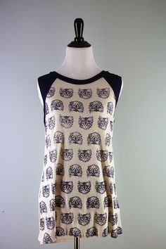 Embrace your inner crazy cat lady with this fun sleeveless top. This made in the USA muscle tank top is covered with the cutest disembodied kitten heads. Tank top has a slight high low hem. The body o