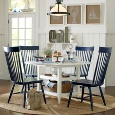 Coastal Room Ideas by Birch Lane: http://www.completely-coastal.com/2016/03/coastal-decor-birch-lane.html Navy blue dining room chairs and white table. Great contrast. Not the overlook... nautical theme wall art that complements the sisal rug.