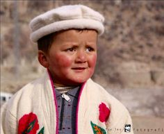 Adorable Hunzai child in traditional pakol (woolly hat) & embroidered gown.