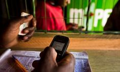 An employee uses a  mobile phone inside an M-Pesa store in Nairobi