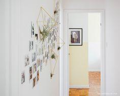 Corredor de um apartamento com pintura divertida, fotos Polaroid e prismas com air plants