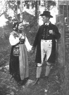 Early 1900's photo of the folk dress of Dalicarlia, Leksand, Sweden. The woman's dress consists of an embroidered bodice with white sleeves, a dark skirt and an apron and an embroidered cap, The man's dress very much resembles that of a church of England parson, apart from the yellow buckskin breeches and garter ornaments.