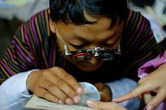 A poorly sighted teenager in Bhutan trying out a high powered magnifier