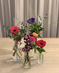 Colourful meadow style table centre created using seasonal stems in varied size bottles
