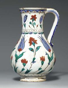 AN IZNIK POTTERY JUG  OTTOMAN TURKEY, CIRCA 1620  Of baluster form on short foot rising to flaring trumpet mouth & with simple loop handle, white body decorated with cobalt-blue, bole-red, black & green, body with alternating large blue tulips & large red flowers, with smaller red flowers between, neck with similar but reduced design, base with stylized ring of imitation marbling, waist slightly protruding, with plait & blue and green fringe...  8¾in.  high