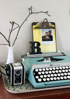 love this typewriter vignette. clipboard w/ paint chips & photo, milk glass, vintage camera & typewriter- all my favorite things!