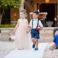 Flower girl wearing a blush pink dress and ring bearer wearing navy blue shorts with suspenders holding a box with the rings down the aisle | Leslie Ann Photography | villasiena.cc