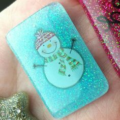 This resin accessory is made with a snowman sticker and epoxy resin in a light blue color.  This piece of snowman jewelry measures 1.5 inches by 1.25 inches.  This rectangle piece is very lightweight. It can be made as the resin piece only with no attachments, which would look pretty as winter decor.  It can be set as a keychain or keyring which comes with a keychain or keyring attachment.  It can be set as an ornament that dangles from a pretty sheer white ribbon.  It can be set as a zipper…