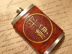 """Hand tooled Leather with the Chinese character """"Serenity"""" highlighted with copper metallic paint over an antique saddle tan. Same flask that was shared on Drunken Moogle.    Please be aware that I am growing tired of making this design and I would like to move on to creating other designs, meaning that this might be the last batch of this Serenity Design that I create."""