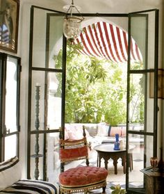 The Winter Garden of Aziyade, a 19th century Orientalist fantasy in Provence. Indian lanterns are hung above Syrian inlaid tables and a Napoleon III chair retaining its original Pink tufted fabric with passementerie. Photographed for World of Interiors by Jean-Francoise Jaussaud.