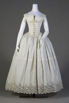 White cotton petticoat, ca. 1838-1842. Before the invention of the cage crinoline formed by steel hoops, as many as six petticoats held out the wide skirts of the late 1840s. By 1850, the expanse of skirt was so great that the waist looked small even without a heavily boned corset. KSUM 1983.1.60.