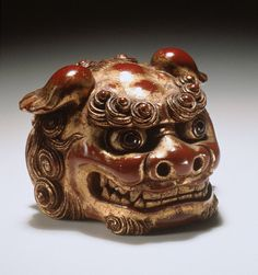 Netsuke ~ Yuso (Japan) Chinese Lion Mask, late 19th century Netsuke, Wood with red and gold lacquer, inlays