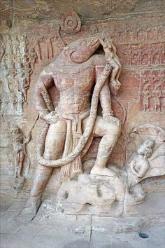 A sculpted panel at the Gupta-period (4th-6th century CE) caves of Udayagiri, Madhya Pradesh, India. The caves are rock-cut Hindu shrines and this panel shows Vishnu as the boar-headed incarnation Varaha. The god rises from the cosmic waters, defeating the primeval serpent monster, and rescuing the goddess Bhudevi (earth), who hangs from his tusk. Photo by: Jean-Pierre Dalbera