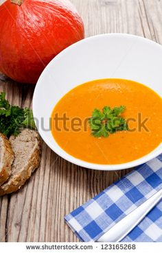 fresh tasty pumpkin soup and bread on wooden table - stock photo