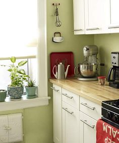 Green kitchen + white cabinets + red accents: 'Sweet Caroline' by Benjamin Moore - the inspiration for my kitchen at home, ikea adel units and paint from brewers, I'll look up the name (must have tried dozens of samples)  Lovely, but I don't k ow if I would keep the red accents or replace them with light turquoise blue and yellow instead.