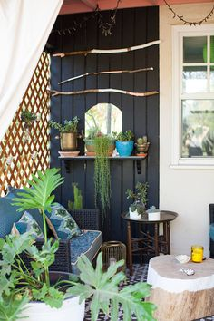 Bohemian patio. Great ideas here! Black accent wall, screen with tea lights, mirror, painted branches.