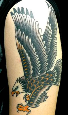 An eagle towers over the skies in this imposing Old School tattoo.