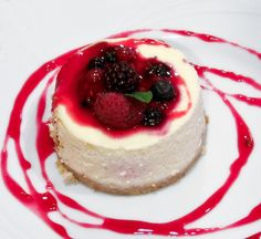 cheese cake with strawberries and raspberry on top.
