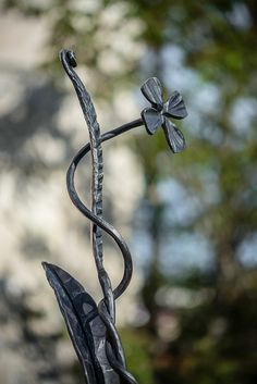 A flower Height: 88cm Stand: 21cm Weight: 6kg Note: a unique design of this art work would be appreciated anytime in the future, notice the details of three same massive metal strips wrought to be entangled together and this creates a very interesting composition.