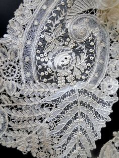 A fine 19THC Brussels lace lappet with large ornate fern on edge worked in Point de Gaze with vignettes filled with Point de Gaze roses.Excellent design and workmanship.Lace part of museum deaccession.