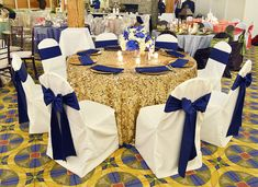We love this color combo for an event or wedding at BayView Event Center. Pictured: Champagne dazzle overlay, gold charger plates with royal blue napkins wraps, white fitted chair covers with matching royal blue satin sashes, and custom fresh floral centerpiece. | Decor by FestivitiesMN.com