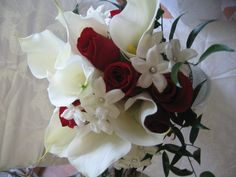 LOVE THIS!!! White calla lillys, charolette red roses and stephonotis make a wonderful elegant combination. The stem of this bouquet was wrapped in white satin and the Groom had a bout made of a red rose and the stephonotis
