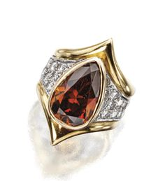 FANCY COLORED DIAMOND RING. The pear-shaped diamond of fancy orange-brown color weighing 5.50 carats, framed by pavé-set round diamonds weighing approximately 1.25 carats, within a fancy-shaped band of 18 karat yellow and white gold,