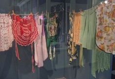 """vintage apron display -- maybe hang a couple """"clothes lines"""" on the wall and use them to display grandmas aprons?"""